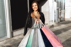 Young smiling girl enjoys a successful shopping, walking down th stock image