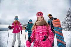 Smiling girl with family on ski slope on vacation in mountain Royalty Free Stock Photography