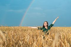Young smiling girl in a field with Golden wheat and rainbow with hands in hand. Young smiling girl in a field with Golden wheat and rainbow with hands in hand royalty free stock photos