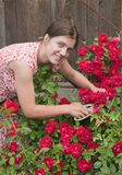 Young smiling girl florists working in the garden Stock Image
