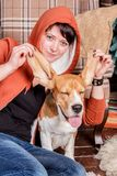 Young smiling girl with funny and silly beagle dog who shows the tongue with closed pleased eyes. Young smiling woman with funny beagle dog who shows the tongue Stock Images