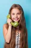 Young smiling girl with green handset Stock Image