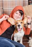 Young smiling girl with happy and silly beagle dog who shows the tongue. Young smiling woman with funny beagle dog who shows the tongue holding its ears are Royalty Free Stock Photography