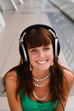 Young smiling girl in headphones. Young pretty girl in big headphones is smiling Stock Photo