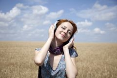 Young  smiling girl with headphones at field. Royalty Free Stock Photography