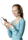 Young smiling girl with headphones with the phone. On a white Royalty Free Stock Image