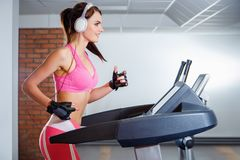 Young smiling girl with headphones running on a treadmill in a sport club. The concept of sport and active lifestyles.  Royalty Free Stock Photo
