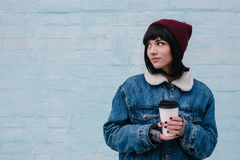 Young smiling girl hipster hot drink in hand, on a light background. Young hipster girl in a blue denim jacket and hot drinks in hand on light background Royalty Free Stock Photo
