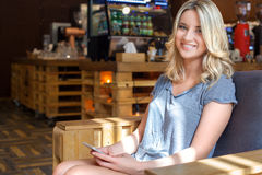 Young smiling girl holding her phone in modern coffee shop Stock Image