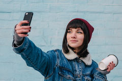 Young smiling girl holding a hipster coffee and photographed on phone. Young smiling girl hipster blue denim jacket and hat, holding a coffee and photographed on Royalty Free Stock Photography