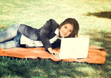 Young and smiling girl with laptop in the park, vintage effect.  Royalty Free Stock Photography