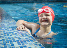 Young smiling girl learning to swim in the pool stock image