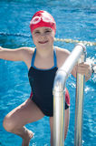 Young smiling girl learning to swim in the pool Royalty Free Stock Photos
