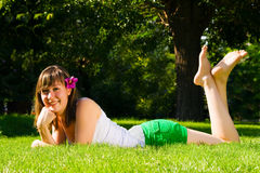 Young smiling girl lies on grass Royalty Free Stock Photo