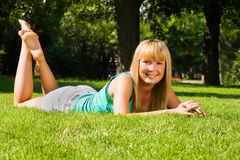 Young smiling girl lies on grass Stock Image