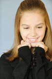 Young smiling girl looks downwards Stock Images