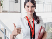 Young Smiling Girl Made Successful Work Shows Gesture Big Thumb Up. Beautiful Smiling Businesswoman Standing Against White Offices Stock Photos