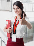 Young Smiling Girl Made Successful Work Shows Gesture Big Thumb Up. Beautiful Smiling Businesswoman Standing Against White Offices Stock Photo