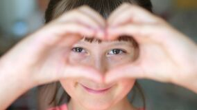 Young smiling girl makes heart sign with her hands