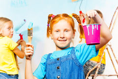 Young smiling girl performs painting accessories Royalty Free Stock Photography