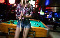 Young smiling girl playing billiard in club. Young smiling sexy girl playing billiard in club stock photos