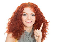 Young smiling girl points finger up. Royalty Free Stock Image