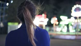 Young smiling girl with ponytail walking forward then turning around smiling and looking at camera hanging out in. Amusement park with attractions background stock footage