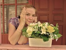 Young smiling girl on porch with a pot of bright flowers Stock Images