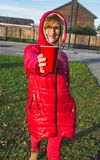 Young smiling girl in red clothes holding red plastic cup in her hands. healthy lifestyle concept - Image. Young smiling blonde girl in red clothes standing on a royalty free stock photos