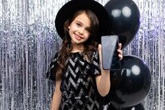 Free Young Smiling Girl Shows A Phone Screensaver With A Mockup At A Party On A Glittery Background Stock Photos - 173251523