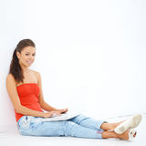 Young smiling girl sitting on the floor with laptop Royalty Free Stock Images