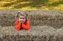 Young smiling girl surrounded by hay bales stock image