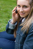 Young smiling girl talking on the phone while sitting down Stock Images