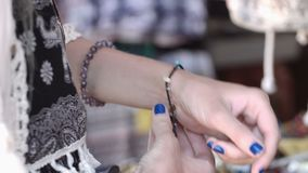 Young smiling girl trying colored bracelets in the store stock video