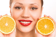 Young smiling girl with two halves of orange. Girl and oranges. Young smiling attractive girl is upholding two halves of one orange beside her face royalty free stock photography