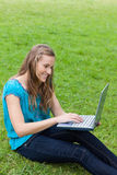 Young smiling girl typing on her laptop Stock Photo