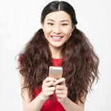 Young smiling girl using cell phone Royalty Free Stock Images