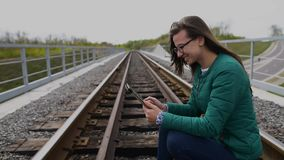 Young smiling girl using tablet and standing at railway. Wearing glasses and dressed in green. stock video footage