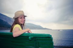 Young girl is sitting on the green bench on background of sea, mountains and gloomy sky. Young smiling girl wearing hat is sitting on the green bench on Royalty Free Stock Photography