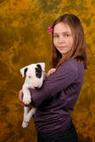 Young smiling girl with white bullterrier puppy. Stock Image