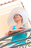 Young smiling girl in a white hat while waiting on the balcony Royalty Free Stock Photography