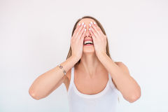 Young smiling girl in white singlet closes her eyes with her hands Stock Photos