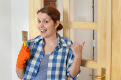 Young smiling girl worker, painting new wooden door Stock Photos