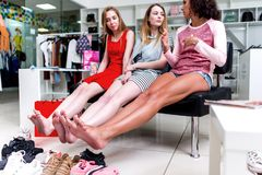 Young smiling girlfriends sitting in a clothing store looking at their bare feet and pile of new shoes and laughing royalty free stock images