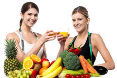 Young smiling girls each holding glass of juice Royalty Free Stock Images