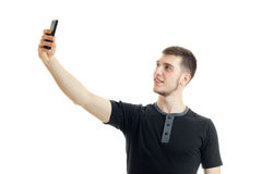 Young smiling guy in the black shirt raised his hand up and makes a photo on phone Stock Photos