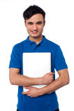 Young smiling guy holding laptop Royalty Free Stock Photos