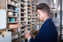 Young smiling guy searching for items in storage Stock Photo