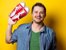 Young smiling guy in shirt with red gumshoes Stock Photos