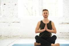 Young smiling guy sitting on a fitness mat and meditating. Young guy with eyes closed sitting on a fitness mat and meditating in the gym Royalty Free Stock Photos